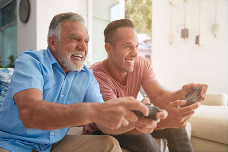 Hispanic Father With Adult Son Sitting On Sofa At Home Playing Video Game Together