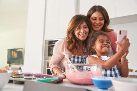 Multi-Generation Hispanic Female Family Taking Selfie Whilst Making Cake In Kitchen Together Stockfoto