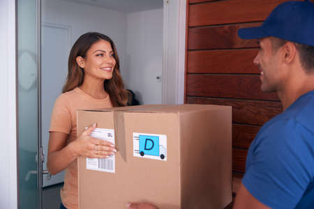 Woman Receiving Package Delivered By Courier To Home