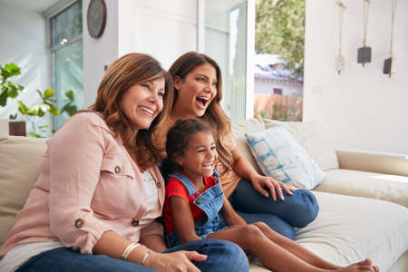 Multi-Generation Female Hispanic Family On Sofa At Home Watching TV Together Stockfoto