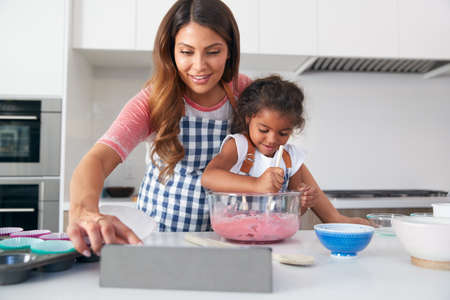 Hispanic Mother And Daughter In Kitchen Following Cake Recipe On Digital Tablet Together