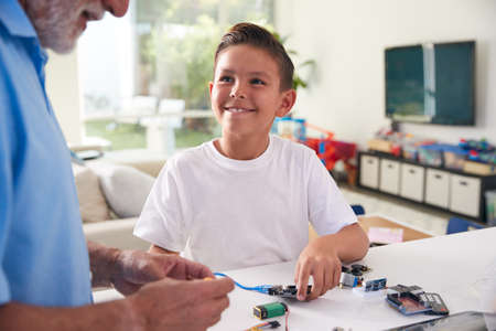 Hispanic Grandson And Grandfather Building Robot From Electronic Components At Home Together