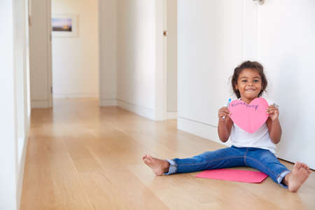 Portrait Of Hispanic Girl Sitting On Floor Making Card For Mothers Day Stockfoto