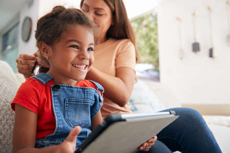 Hispanic Daughter Plays With Digital Tablet Whilst Mother Does Hair At Home
