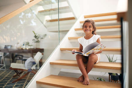 Portrait Of Hispanic Girl Sitting On Staircase In Modern Home Reading Book