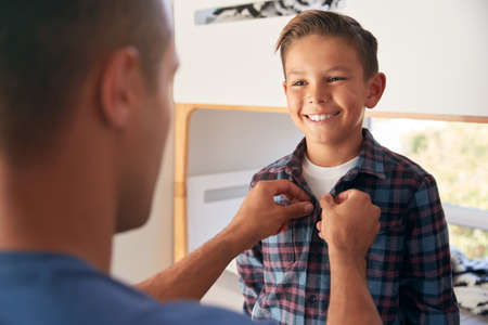Hispanic Father Helping Son To Get Dressed In Bedroom In Morning Stockfoto
