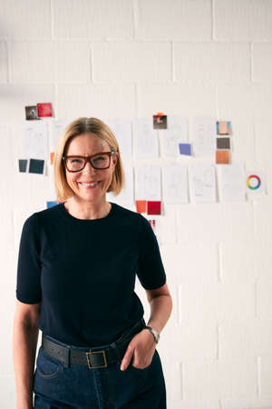 Portrait Of Mature Woman Standing In Front Of Designs On Wall In Start Up Fashion Business