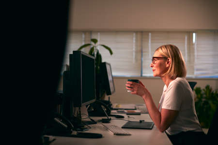 Mature Businesswoman Using Computer Sitting At Desk In Office Working Late