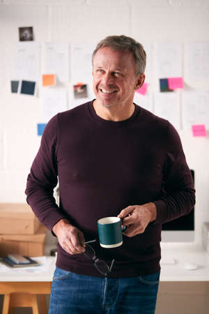 Mature Businessman With Coffee Standing In Front Of Desk In Start Up Creative Business