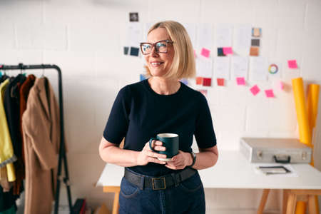 Portrait Of Mature Businesswoman Standing In Front Of Designs And Desk In Start Up Fashion Business