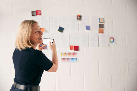 Female Designer Taking Photos Of Designs On Wall With Mobile Phone In Start Up Fashion Business