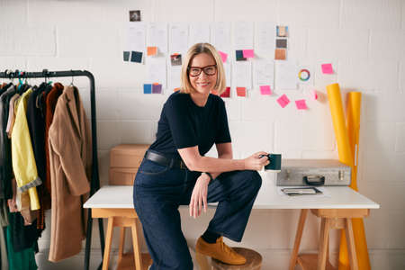 Portrait Of Confident Mature Businesswoman Sitting On Desk In Start Up Fashion Business Stockfoto