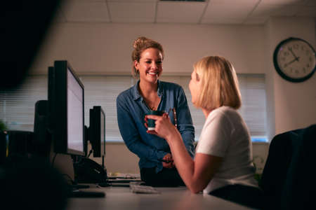 Two Businesswoman Having Informal Meeting Sitting At Desk In Office Working Late Archivio Fotografico