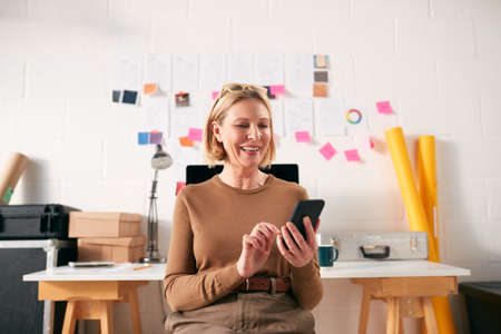 Mature Businesswoman With Mobile Phone Working At Desk In Start Up Creative Business