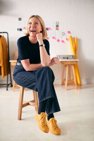 Laughing Mature Businesswoman Sitting On Stool In Front Of Desk In Start Up Fashion Business