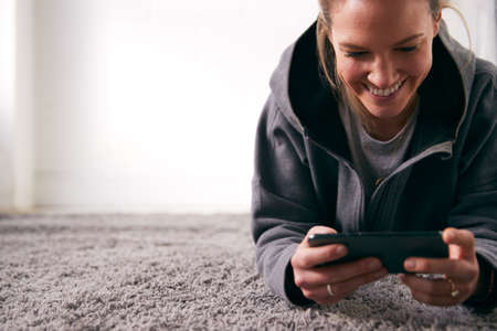 Woman Relaxing At Home Looking At Social Media And Text Messages On Mobile Phone Lying On Carpet Stockfoto