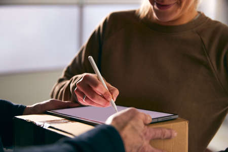 Woman Signing For Courier Delivery To Office Using Digital Tablet