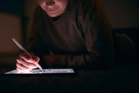 Close Up Of Woman Drawing On Digital Tablet Using Stylus Pen Lying On Carpet At Night Archivio Fotografico