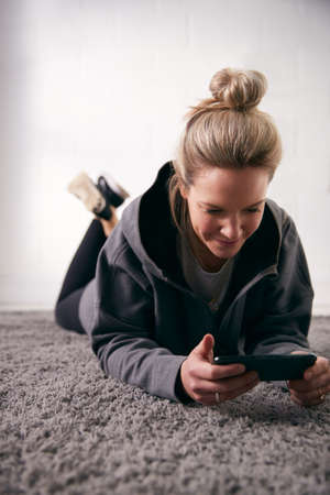 Woman Relaxing At Home Looking At Social Media And Text Messages On Mobile Phone Lying On Carpet Archivio Fotografico