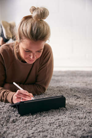 Woman Drawing On Digital Tablet Using Stylus Pen Lying On Carpet At Home