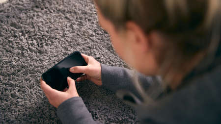 Overhead Shot Of Woman Looking At Screen With Copy Space On Mobile Phone Lying On Carpet Archivio Fotografico
