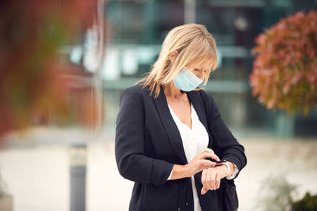 Mature Businesswoman Wearing PPE Face Mask Checking Smart Watch In Street During Health Pandemic