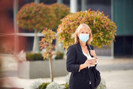 Mature Businesswoman With Takeaway Coffee Wearing PPE Face Mask In Street During Health Pandemic