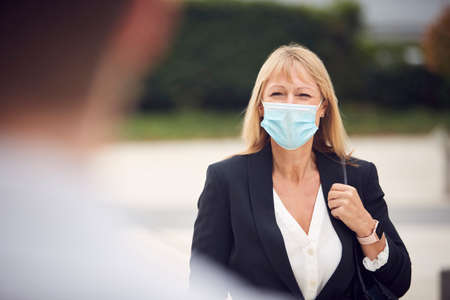 Mature Businesswoman Wearing PPE Face Mask Meeting Colleague In Street During Health Pandemic Archivio Fotografico