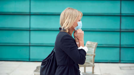 Mature Businesswoman Putting On PPE Face Mask Walking Outdoors In Street During Health Pandemic Archivio Fotografico