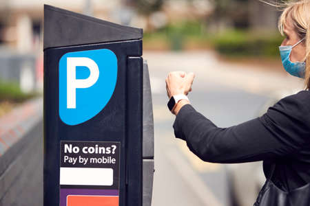 Businesswoman Wearing PPE Face Mask Makes Contactless Payment For Car Parking With Smart Watch