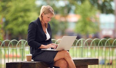 Mature Businesswoman Sitting On City Park Bench Working On Laptop Archivio Fotografico