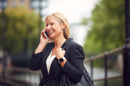 Mature Businesswoman Talking On Mobile Phone As She Walks Through City Street