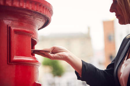 Close Up Of Businesswoman Posting Letter Into City Mailbox