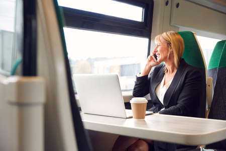Businesswoman On Train Working On Laptop And Talking On Mobile Phone