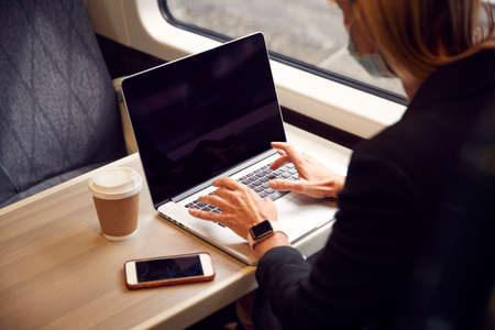 Close Up Of Businesswoman On Train Working On Laptop Wearing PPE Face Mask During Health Pandemic