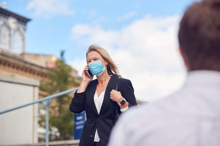 Mature Businesswoman With Mobile Phone Wearing PPE Face Mask Walks In Street During Health Pandemic