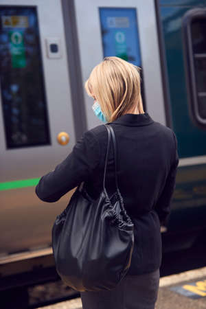 Businesswoman On Railway Platform Waiting To Board Train Wearing PPE Face Mask In Health Pandemic