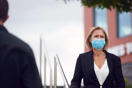Mature Businesswoman Wearing PPE Face Mask Walking Outdoors In Street During Health Pandemic Archivio Fotografico
