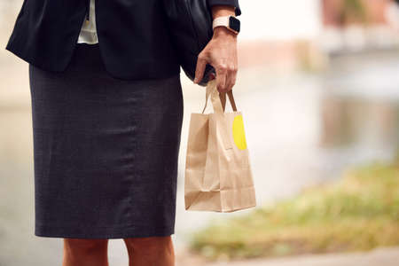 Close Up Of Businesswoman Carrying Takeaway Work Lunch In Paper Bag