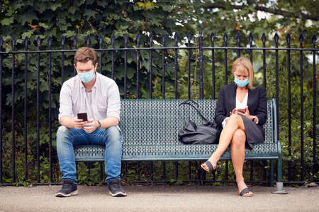 Passengers On Railway Platform With Mobile Phone Wearing PPE Face Mask During Health Pandemic 免版税图像