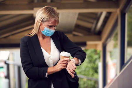 Businesswoman At Railway Station Checking Smart watch Wearing PPE Face Mask During Health Pandemic