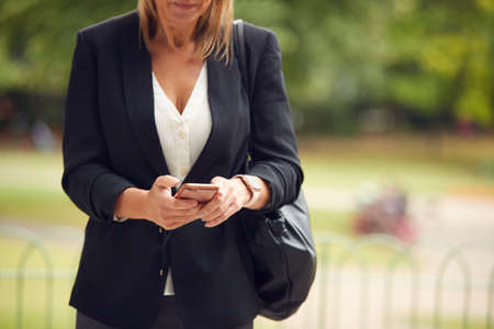 Close Up Of Businesswoman Checking Messages On Mobile Phone Walking In City Park