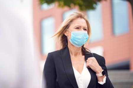 Mature Businesswoman Wearing PPE Face Mask Walking Outdoors In Street During Health Pandemic 免版税图像