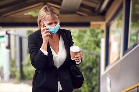 Businesswoman At Railway Station Talks On Mobile Phone Wearing PPE Face Mask During Health Pandemic