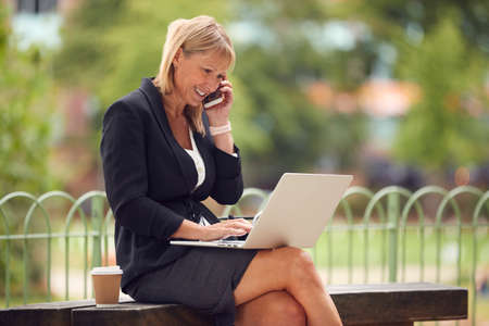 Mature Businesswoman Sitting On City Park Bench Working On Laptop And Talking On Mobile Phone
