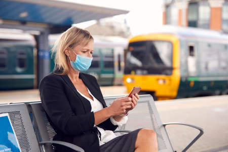Businesswoman On Railway Platform With Mobile Phone Wearing PPE Face Mask During Health Pandemic