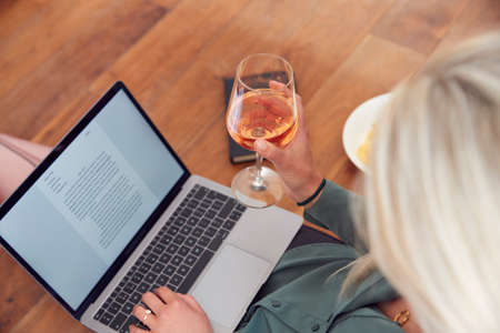 Close Up Of Businesswoman At End Of Day With Wine In Loungewear And Suit On Laptop Working At Home
