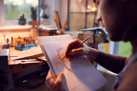 Close Up Of Male Jeweller Sketching Out Design For Ring In Studio