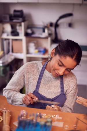 Female Jeweller At Bench Working On Ring With File In Studio