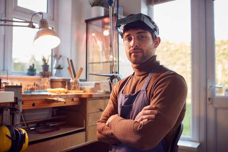 Portrait Of Male Jeweller Wearing Headband Magnifiers Working In Studio
